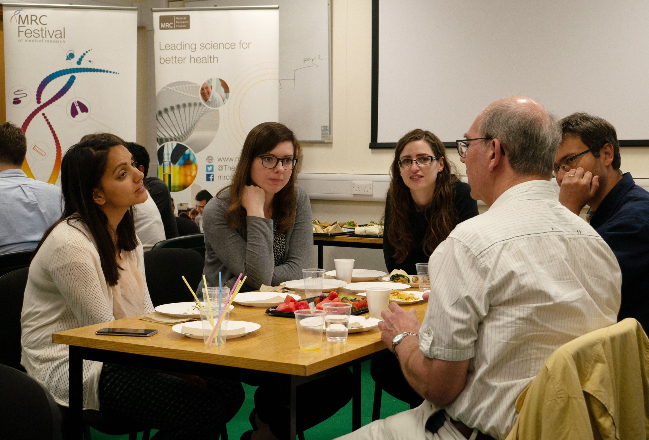Lay members of Parkinson's UK chat over lunch with the Unit's early-career scientists.