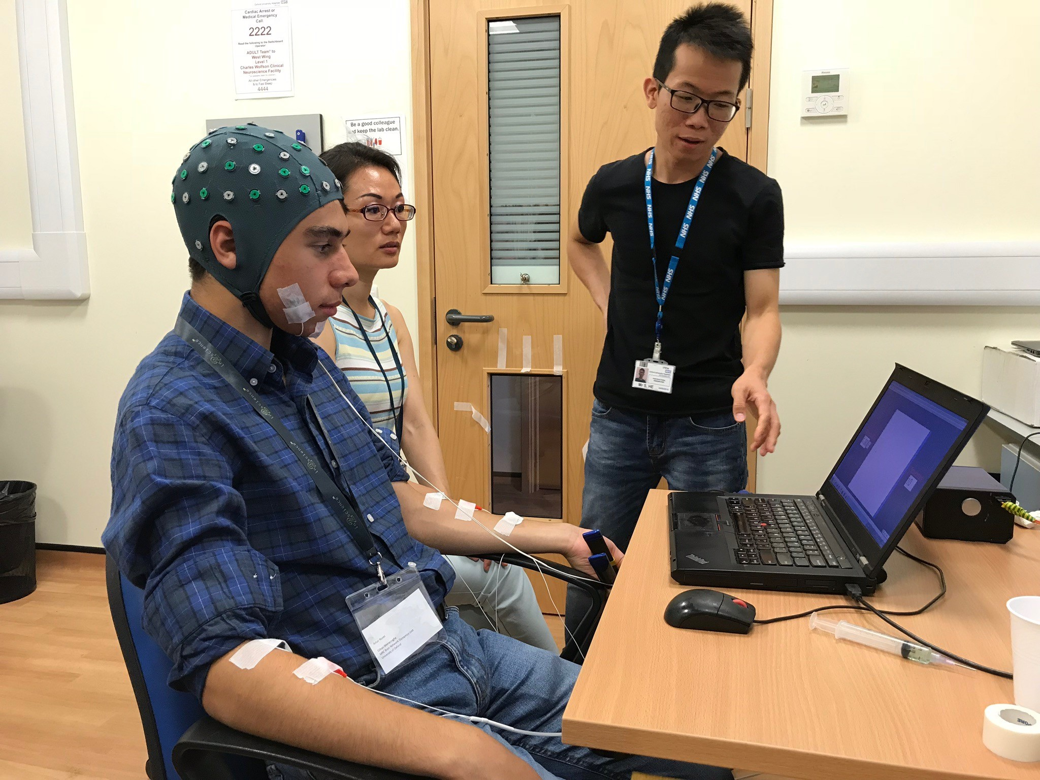 In2scienceUK student Artur records his own brain and muscle activity at the MRC BNDU, guided by Unit scientists Huiling Tan (seated) and Shenghong He.