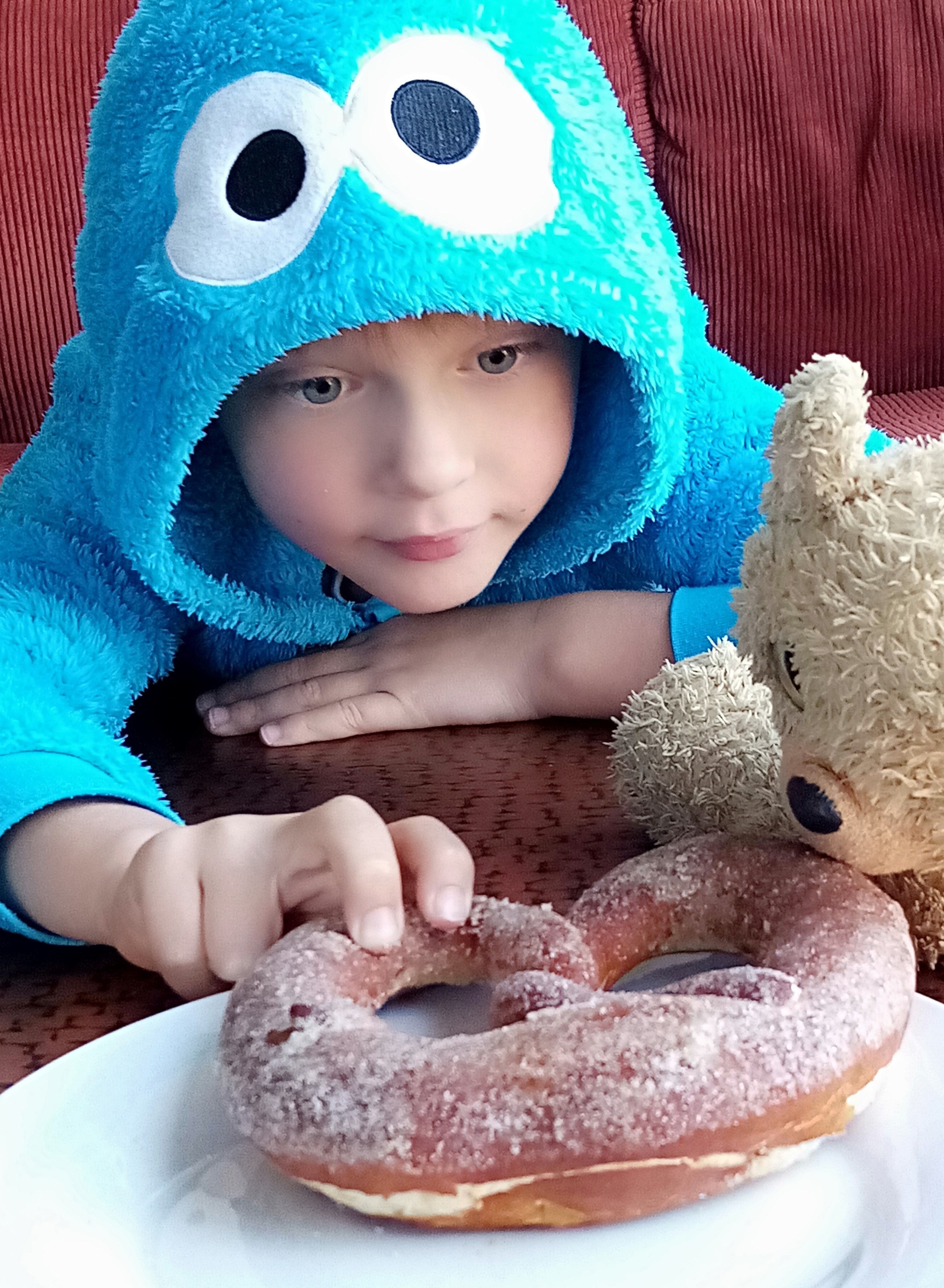 Picture of young boy reaching for a doughnout on a plate.
